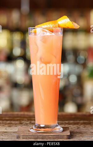 Refreshing cocktail with grapefruit is on the bar in a nightclub on a blurry background of bottles with alcohol - Stock Photo