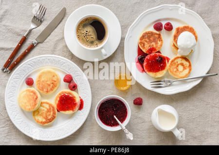 Breakfast table with pancakes and coffee. Cottage cheese pancakes with raspberry jam and sour cream, cup of black coffee and cream. Table top view, ta - Stock Photo