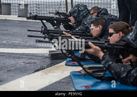 151114-N-UF697-245 EAST CHINA SEA (Nov. 14, 2015) Sailors participate in a M16 live-fire exercise on the flight deck of the forward-deployed Arleigh Burke-class guided missile destroyer USS Stethem (DDG 63). Stethem is on patrol in the 7th Fleet area of operation in support of security and stability in the Indo-Asia-Pacific. (U.S. Navy photo by Mass Communication Specialist 2nd Class Kevin V. Cunningham/Released) - Stock Photo