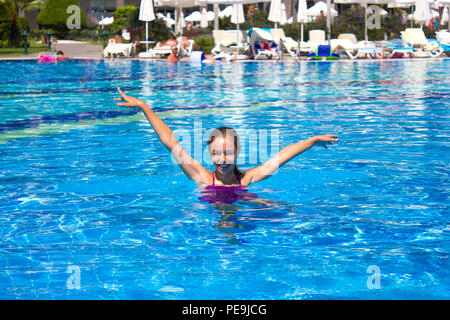 KEMER, ANTALYA, TURKEY - 19 JULY, 2018: Large pool in the Barut Hotel with swimming people under blue summer sky - Stock Photo