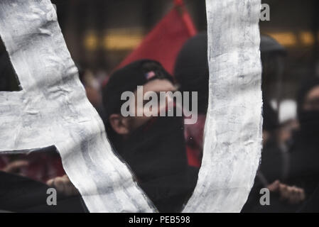 Washington D.C, USA. 12th Aug, 2018. A member of Antifa at the Unite the Right 2 rally in Washington, DC on August 12 seen through an anti-Alt-Right banner.Despite predictions of a huge rally by the Alt-Right celebrating the first anniversary of the Unite The Right rally in Charlottesville, Virginia, only 15 showed up to march in Washington, DC on Saturday August 12. The small group was met by over a thousand anti-fascist protesters who marched from the city's Freedom Plaza to meet the handful of white supremacists who gathered under police guard under at a park behind the Whi - Stock Photo