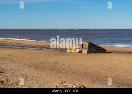 North sea coast in Caister-on-Sea, Norfolk, England, UK -  with an old bunker on the beach - Stock Photo