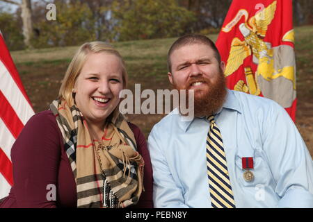 Retired US Marine Corps Cpl. Brandon Burns and his wife Laura pose for a photo after his Good Conduct Medal presentation at the Wounded Warrior Regiment Headquarters, Marine Corps Base Quantico, Va., Nov. 18, 2015. Burns was presented the award nine years after medically retiring from the Marine Corps. (US Marine Corps photo by 1st Lt. Andrew Bolla/Released) - Stock Photo