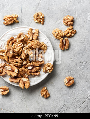 Walnut kernels on white plate over gray background. - Stock Photo