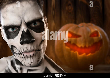 Portrait of young man on Halloween with burning pumpkin in hand isolated on white background. Bloody Halloween theme: The crazy dead face. - Stock Photo