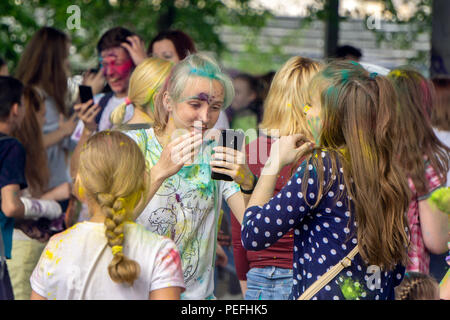 DZERZHINSK, RUSSIA - MAY 19, 2018: Happy young girl is checking her face using smartphone on festival of Holi colors and music. - Stock Photo
