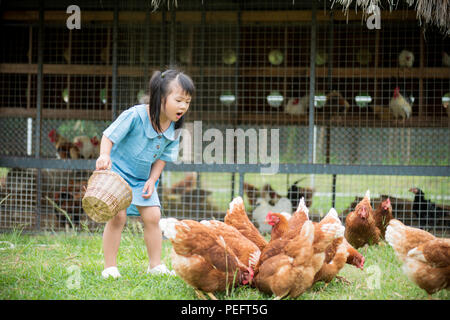 Happy little girl feeding chickens in front of chicken farm. Summer activities for kids. - Stock Photo