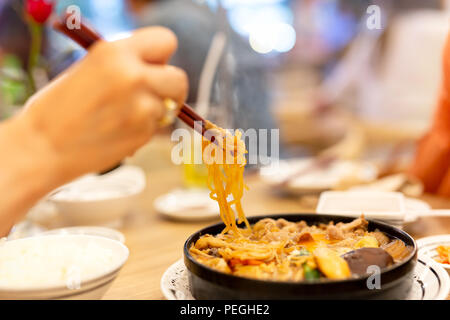 Hand with chopsticks eating Japanese udon noodles. - Stock Photo