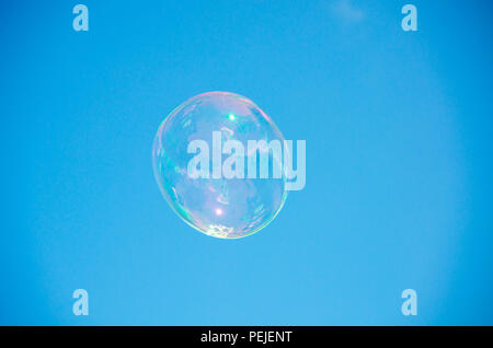 Transparent soap or water bubbles with blue sky background - Stock Photo