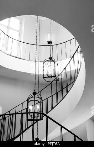 old antique spiral staircase leading upwards against the background of a glowing window - Stock Photo