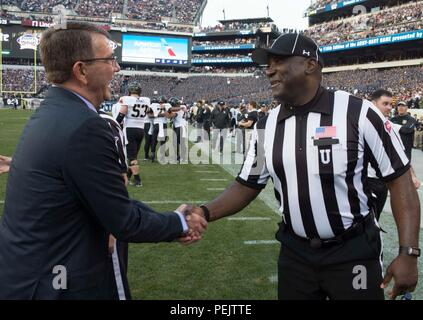 Secretary of Defense Ash Carter shakes hands with a referee at the 2015 Army Navy game in Philadelphia, Dec 12, 2015.  (DoD photo by Mass Communication Specialist 1st Class Tim D. Godbee)(Released) - Stock Photo