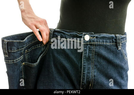 Closeup of a slim woman waist in oversized pants after losing a lot of weight. Over white background. - Stock Photo