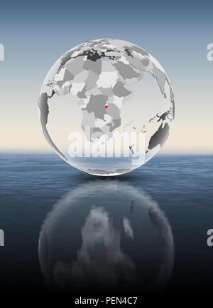 Burundi in red on translucent globe floating above water. 3D illustration. - Stock Photo