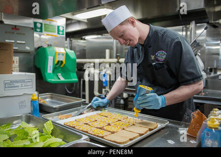 160112-N-YO638-002 YOKOSUKA, Japan (Jan. 12, 2016) Culinary Specialist 3rd Class Robert Lockerman, from Milton, Del., prepares sandwiches for Sailors aboard the U.S. Navy's only forward-deployed aircraft carrier USS Ronald Reagan (CVN 76). Lockerman works in Reagan's aft galley, where culinary specialists prepare food for more than 1,500 Sailors daily while in port. Ronald Reagan provides a combat-ready force that protects the collective maritime interested of its allies and partners in the Indo-Asia Pacific Region. (U.S. Navy photo by Mass Communication Specialist 3rd Class Cody Hendrix/Relea - Stock Photo