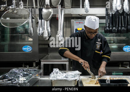 160112-N-YO638-052 YOKOSUKA, Japan (Jan. 12, 2016) Culinary Specialist 3rd Class Sha-vasia Thomas, from Brooklyn, N.Y., prepares chicken aboard the U.S. Navy's only forward-deployed aircraft carrier USS Ronald Reagan (CVN 76). Thomas works in Reagan's wardroom, where culinary specialists prepare food for more than 50 officers daily while in port. Ronald Reagan provides a combat-ready force that protects the collective maritime interested of its allies and partners in the Indo-Asia Pacific Region. (U.S. Navy photo by Mass Communication Specialist 3rd Class Cody Hendrix/Released) - Stock Photo