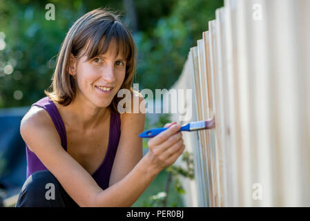 Smiling woman painting a garden fence with a paintbrush in a concept of DIY and yard maintenance. - Stock Photo