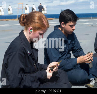 SOUTH CHINA SEA (January 30, 2016)- Electronics Technician 3rd Class Elizabeth Hornbeck, left, and Electronics Technician 3rd Class Ricardo Arellano, assigned to amphibious dock landing ship USS Ashland (LSD 48) load M16 magazines during a live fire exercise on the flight deck. Ashland is assigned to the Bonhomme Richard Amphibious Ready Group and is enroute to participate in Cobra Gold, a Thai-U.S. co-sponsored multinational joint exercise designed to advance regional security by exercising a robust multinational force from nations sharing common goals and security commitments in the Indo-Asi - Stock Photo