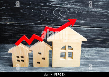 Wooden houses stand in a row from small to large with a red arrow up. concept of high demand for real estate. increase energy efficiency of housing. r - Stock Photo