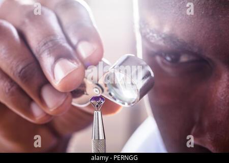Close-up Of Jeweler Examining Diamond Through Loupe - Stock Photo