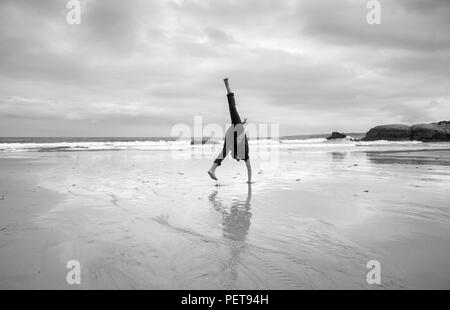 young man doing acrobatics on a beach - Stock Photo