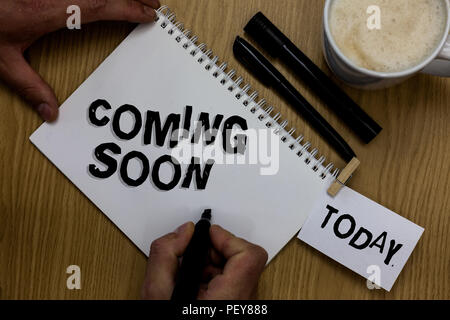 Writing note showing Coming Soon. Business photo showcasing something is going to happen in really short time of period Man holding marker notebook cl - Stock Photo