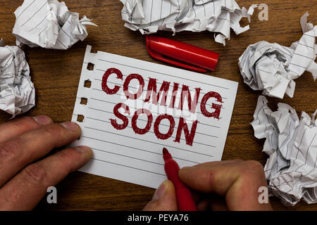 Writing note showing Coming Soon. Business photo showcasing something is going to happen in really short time of period Man holding marker notebook pa - Stock Photo