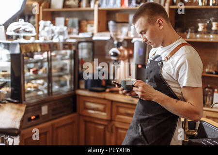 handsome bartender drinking coffee and texting message in the smart phone. communication concept - Stock Photo