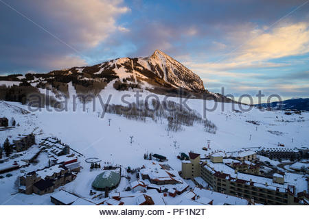 Alpenglow on Crested Butte Mountain towering over the ski base area of Crested Butte Mountain Resort in Colorado. - Stock Photo