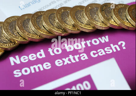 LOAN LEAFLETS WITH ONE POUND COINS RE BORROWING SHORT TERM LOANS PAYDAY APR EXTRA CASH UK - Stock Photo