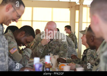 Command Sgt. Maj. Harry J. Buchanan, senior enlisted advisor to Pennsylvania's adjutant general, enjoys dinner chow with Soldiers from the 213th Regional Support Group, Pennsylvania National Guard Aug. 10 at the National Training Center, Fort Irwin, Calif. Troops from the 213th RSG support the 56th Stryker Brigade Combat Team, 28th Infantry Division during the training rotation at NTC. (US Army National Guard photo by Sgt. Claire A. Charles) - Stock Photo