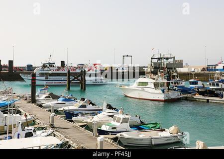 LANZAROTE, SPAIN - APRIL 18, 2018: Muelle de Playa Blanca harbor with ferry and ships, Lanzarote, Canary Islands, Spain - Stock Photo