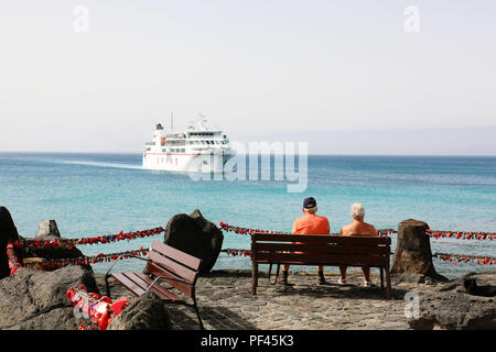 LANZAROTE, SPAIN - APRIL 18, 2018: couple of senior tourists sitting on a bench looking to a big ship coming on Playa Blanca harbor, Lanzarote, Canary - Stock Photo