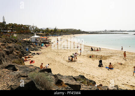 LANZAROTE, SPAIN: APRIL 18, 2018: beautiful view of Playa Dorada beach with bathers on the sand, Lanzarote, Canary Islands - Stock Photo