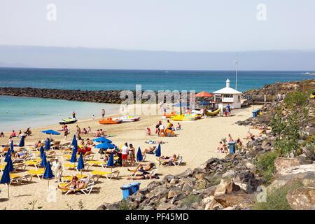 LANZAROTE, SPAIN - APRIL 18, 2018: bathers in Playa Dorada a beach in the south of Lanzarote Island, Canary Islands - Stock Photo