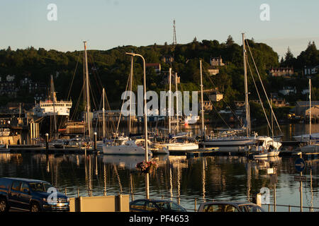 Yachts and the CalMac ferry 'Isle of Mull' settled in for the night as the sun sets over the West Highland port of Oban, Scotland - Stock Photo