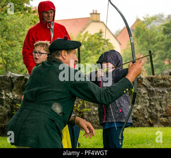 Haddington, UK. 19 August 2018.  The Royal Company of Archers, a ceremonial unit known as the Queen's Bodyguard For Scotland stages a clout archery shoot as part of Haddington 700 events taking place during 2018 to celebrate the granting of a charter by Robert the Bruce to the town in 1318, confirming Haddington's right to hold a market and collect customs. Children also had a chance to try archery. A young girl gets instruction from one of the company's archers - Stock Photo