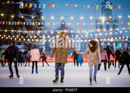 Young couple in love Caucasian man with blond hair with long hair and beard and beautiful woman have fun, active date ice skating on the ice arena in  - Stock Photo