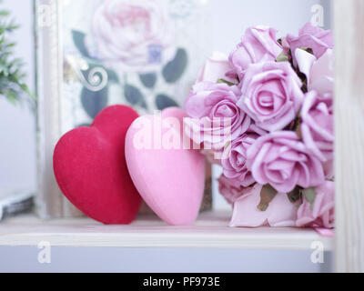 White fireplace in the interior with decorations and decorative elements on Valentine's Day - Stock Photo