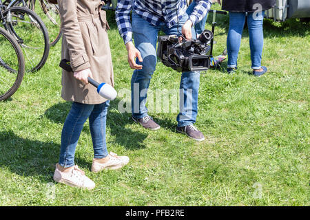 TV reporters working outdoors. Journalsit and cameraman making report at street on bright sunny day - Stock Photo