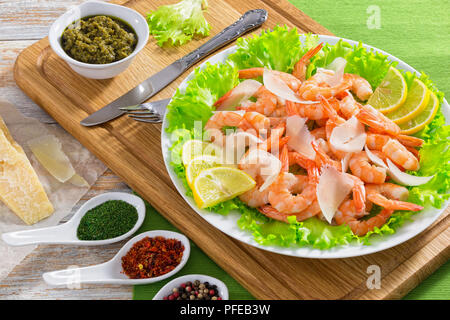 delicious fresh salad with prawns, green lettuce, slices of parmesan cheese and lemon on white plate. Piece of parmesan and sauce pesto on wooden plan - Stock Photo
