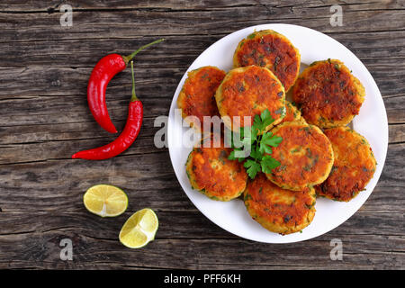 delicious fresh fried homemade fish cakes with mashed potato on plate with lime slices on dark wooden table, classic recipe, view from above - Stock Photo