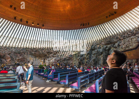 Helsinki Temppeliaukio Church, a tourist inside the Temppeliaukion Kirkko or 'Rock Church' in central Helsinki gazes at its huge copper roof, Finland. - Stock Photo
