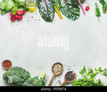Fresh raw greens, unprocessed vegetables and grains over light grey marble kitchen countertop, top view, copy space. Clean eating, healthy, vegan, veg - Stock Photo