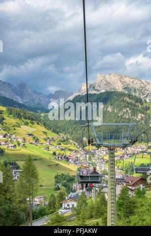 People in a chair lifts down to Santa Cristina in val gardena, Italy - Stock Photo