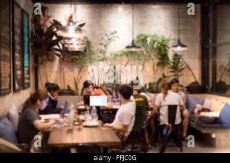 Education concept on blurred students doing home work in cafe shop - Stock Photo