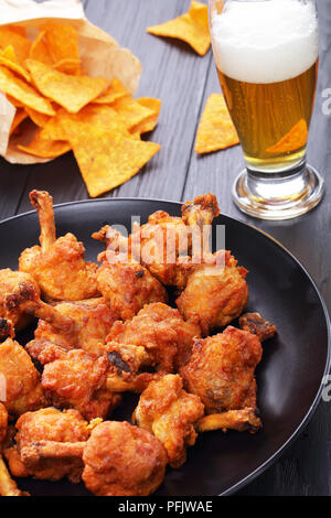 delicious deep fried battered crispy chicken wings with exposed bones on a black plate on dark wooden table. glass of fresh beer and nachos in paper b - Stock Photo