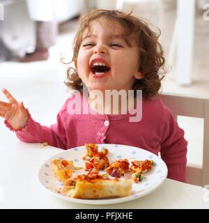 Girl sitting at table laughing, plate of chicken enchiladas in front of her, close-up - Stock Photo