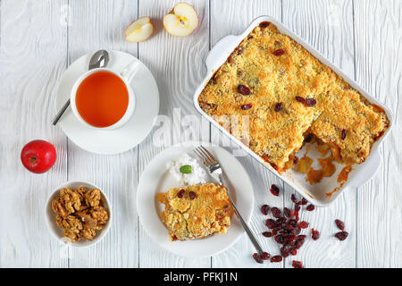 breakfast set -  apple crumble or apple crisp in baking dish and a portion on plate with coconut cream and  cup of tea on table, view from above, clos - Stock Photo