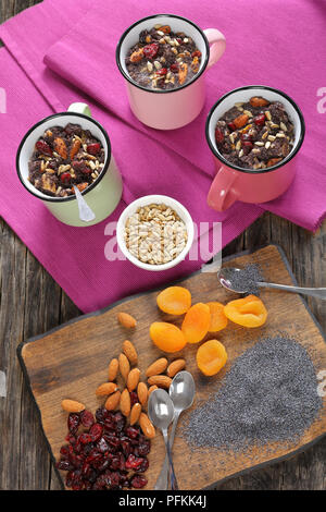 delicious christmas sweet dessert or kutya of poppy seeds mixed with cooked whole wheat, dried fruits and nuts served in cups. ingredients on cutting  - Stock Photo