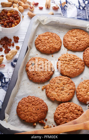freshly baked Oatmeal Cookies with orange zest, raisins and peanuts on a baking sheet with wooden spatulas and kitchen towel, view from above, close-u - Stock Photo